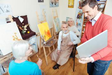 Joyful man showing laptop to colleagues in painting studio