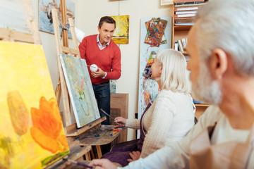 Delighted man teaching people in painting studio.