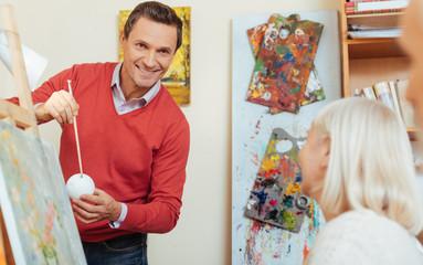 Smiling man teaching people in painting studio.