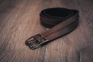 leather belts in wooden background