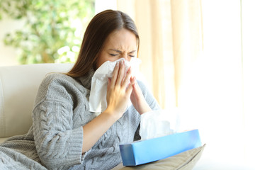 Woman blowing with flu in winter