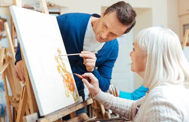 Serious artist helping elderly woman in painting school