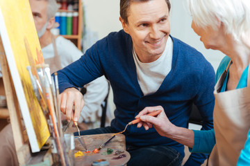 Friendly artist helping elderly woman in painting