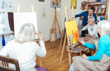 Group of people having lesson in painting school