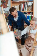 Smiling artist helping elderly man in painting