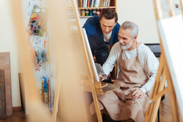 Handsome artist helping elderly man in painting