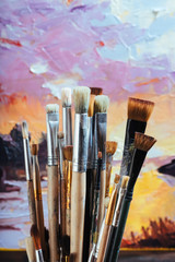 Close up of professional brushes and colorful canvas