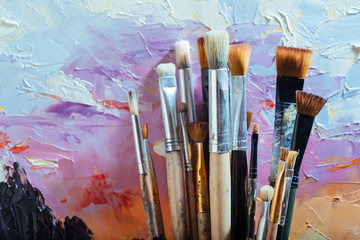 Close up of painting brushes and colorful canvas