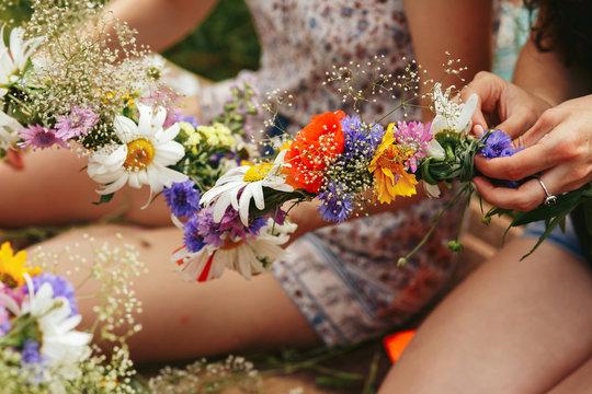 Young hipster women making flower wreaths circle closeup