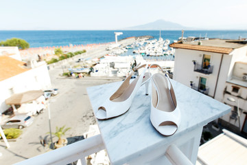 White wedding shoes stand on marble pillar