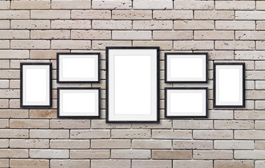 Collage of wooden frames on decorative design bricks wall. Interior decor mock up