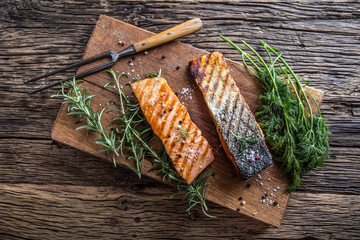 Salmon fillets. Grilled salmon, sesame seeds herb decoration on vintage pan or black slate board. fish roasted on an old wooden table.Studio shot.