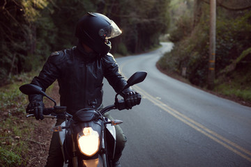 Male astride motorbike on road, looking over shoulder