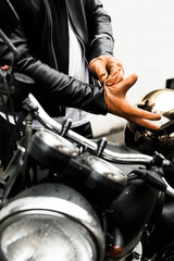 Motorcyclist putting on leather gloves, standing beside motorbike