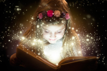 Beautiful little girl reading magic book