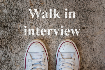 old sneaker on cement floor with walk in interview text