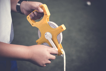 Boy hand holding sport measuring tape or sport equipment tape measure at sport field. Sport equipment measure concept.