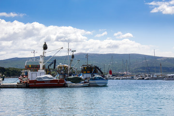 Port with ships in Krk, croatia in the summer with white clouds in the blue sky