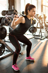 Attractive fit woman in gym exercising with weights.