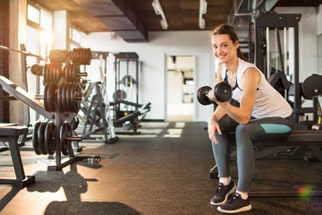 Young woman exercising with dumbbells in gym.