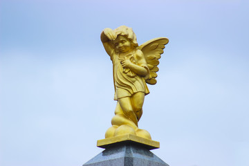 Ancient sculpture of crying angel against the blue sky.