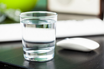 Transparent glass of water. On a dark table. For your design.