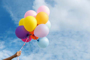 hand of woman holding colorful balloons