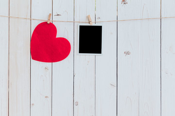 Red heart and photo frame blank hanging at clothesline on wood w
