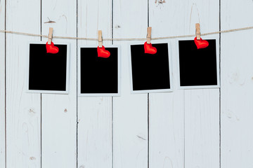 Four photo frame blank and red heart hanging on white wood backg