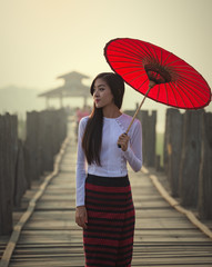 Myanmar woman in traditional dress walking on the u bein bridge