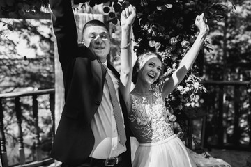 Cheerful newlyweds raise their hands up standing on porch outsid