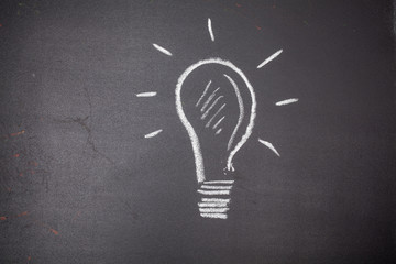 Light bulb. Idea. Drawing on the chalk board. For your design.