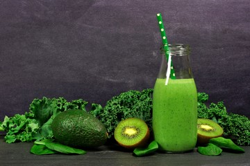 Green smoothie in a milk bottle with kale, avocado, spinach and kiwi against a dark slate background
