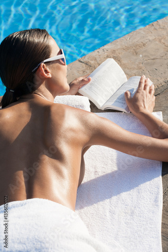 belle femme qui lit allong e au bord d 39 une piscine immagini e fotografie royalty free su. Black Bedroom Furniture Sets. Home Design Ideas