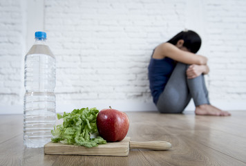 woman or teenager girl sitting on ground alone worried at home suffering nutrition eating disorder