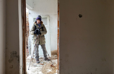 Photographer shooting in a ruined abandoned apartment