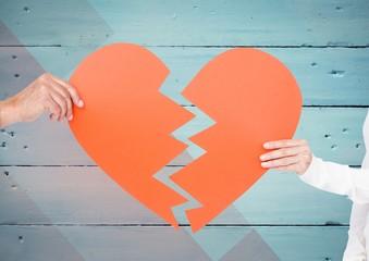 Couple hands holding broken heart against wooden background