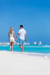 Romantic couple walking on beach and enjoying life