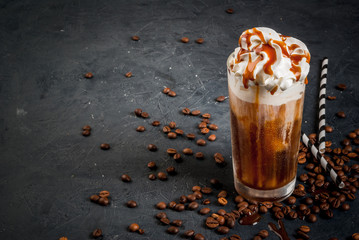 Cold coffee drink frappe (frappuccino), with whipped cream and caramel syrup, with straws and grains of coffee on a dark gray stone table, copy space