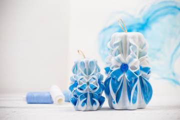 St. Valentine's Day: two carved candles of blue color against the background heart.