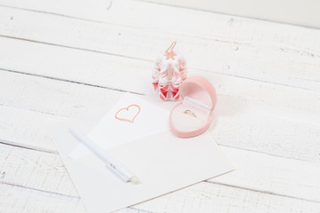 St. Valentine's Day: the offer on a romantic appointment. Two carved candles, pink box and note.