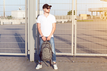 Portrait of stylish young adult man in black cap and sunglasses holding a backpack in hands.Urban city concept.