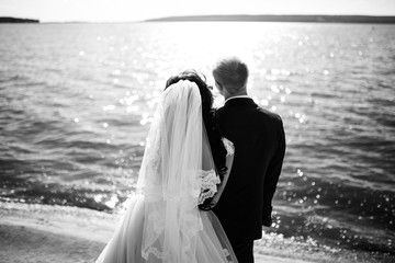 bride and groom standing in front of the lake and looking into the distance. Black and white.