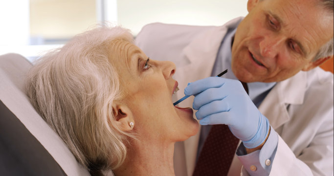 Friendly senior dentist examining elderly woman's teeth