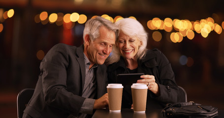 Modern Senior couple looking at photos on their smartphone