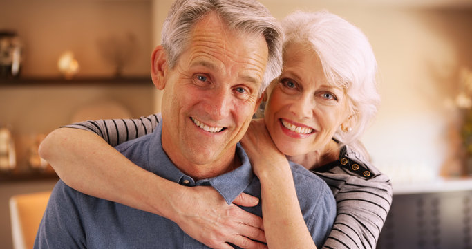 Happy elderly couple sitting at home smiling at camera