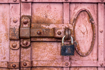 Lock with a latch on an old metal door in red