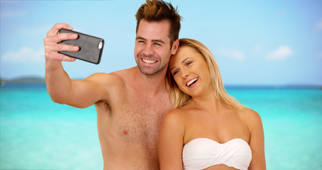 Young social media obsessed couple taking selfies to post online