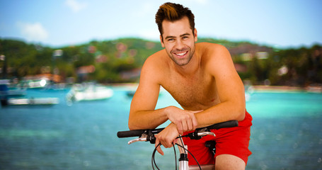 Young hot millennial sitting on bike smiling at camera