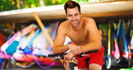 Attractive millennial guy sitting on bike smiling at camera